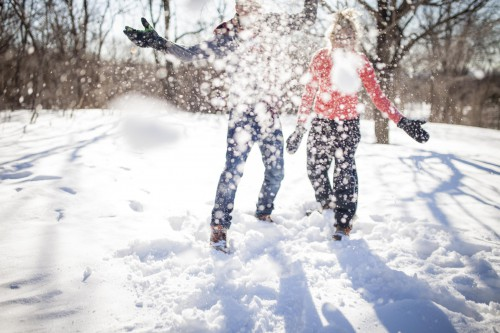 Young couple having a snowball fight and throwing snow in park