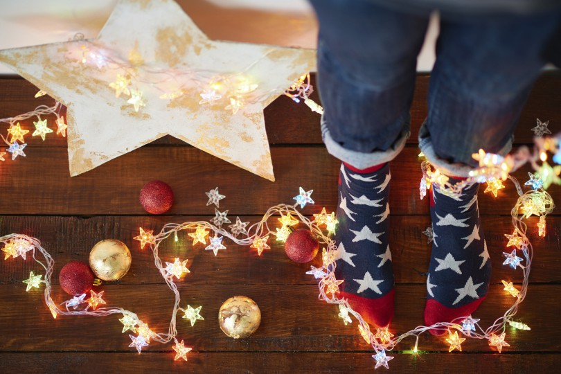 High angle view of feet in socks with stars and Christmas decorations